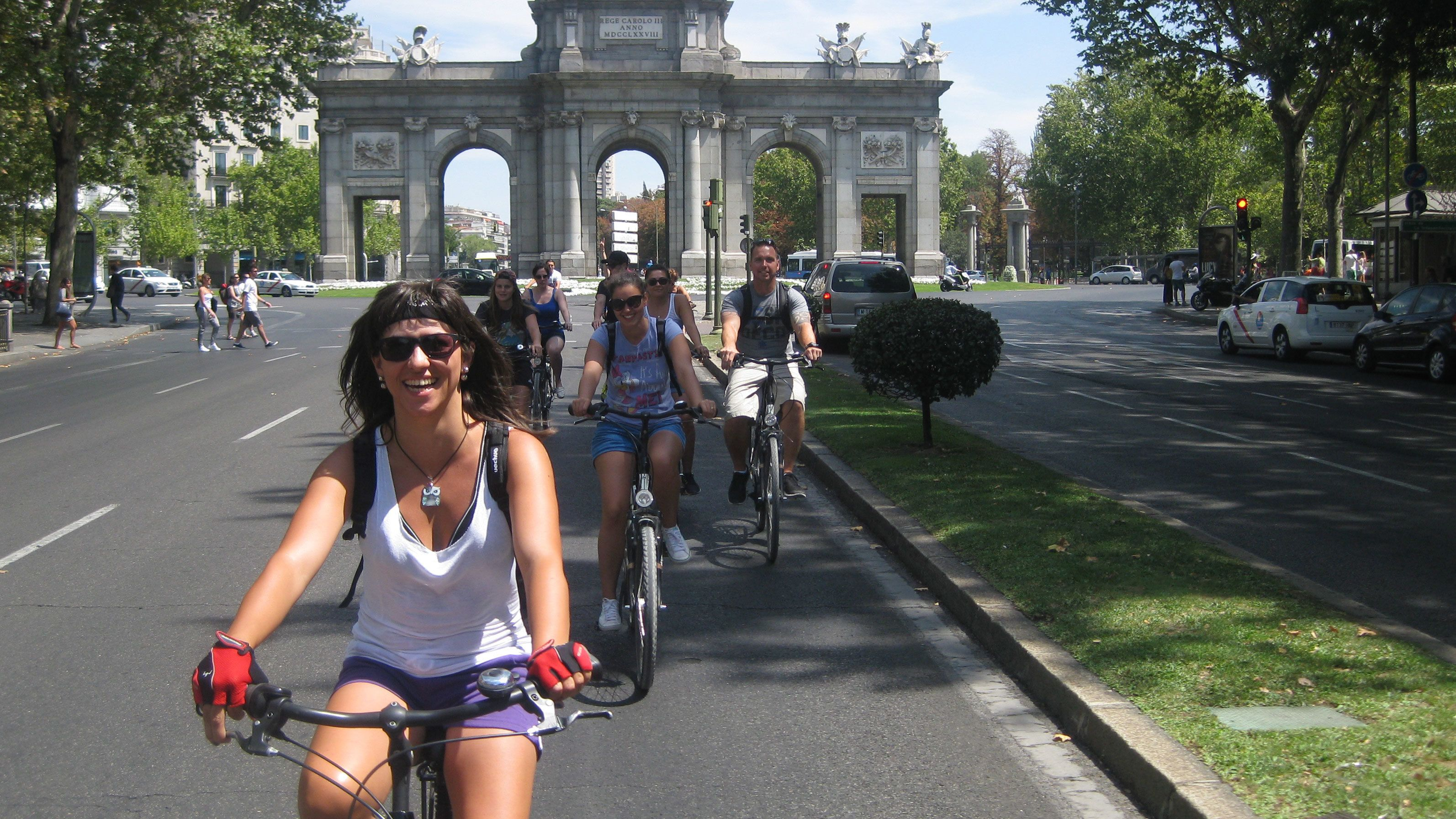 A group of bicyclists riding through Puerta de Alcalá in Madrid