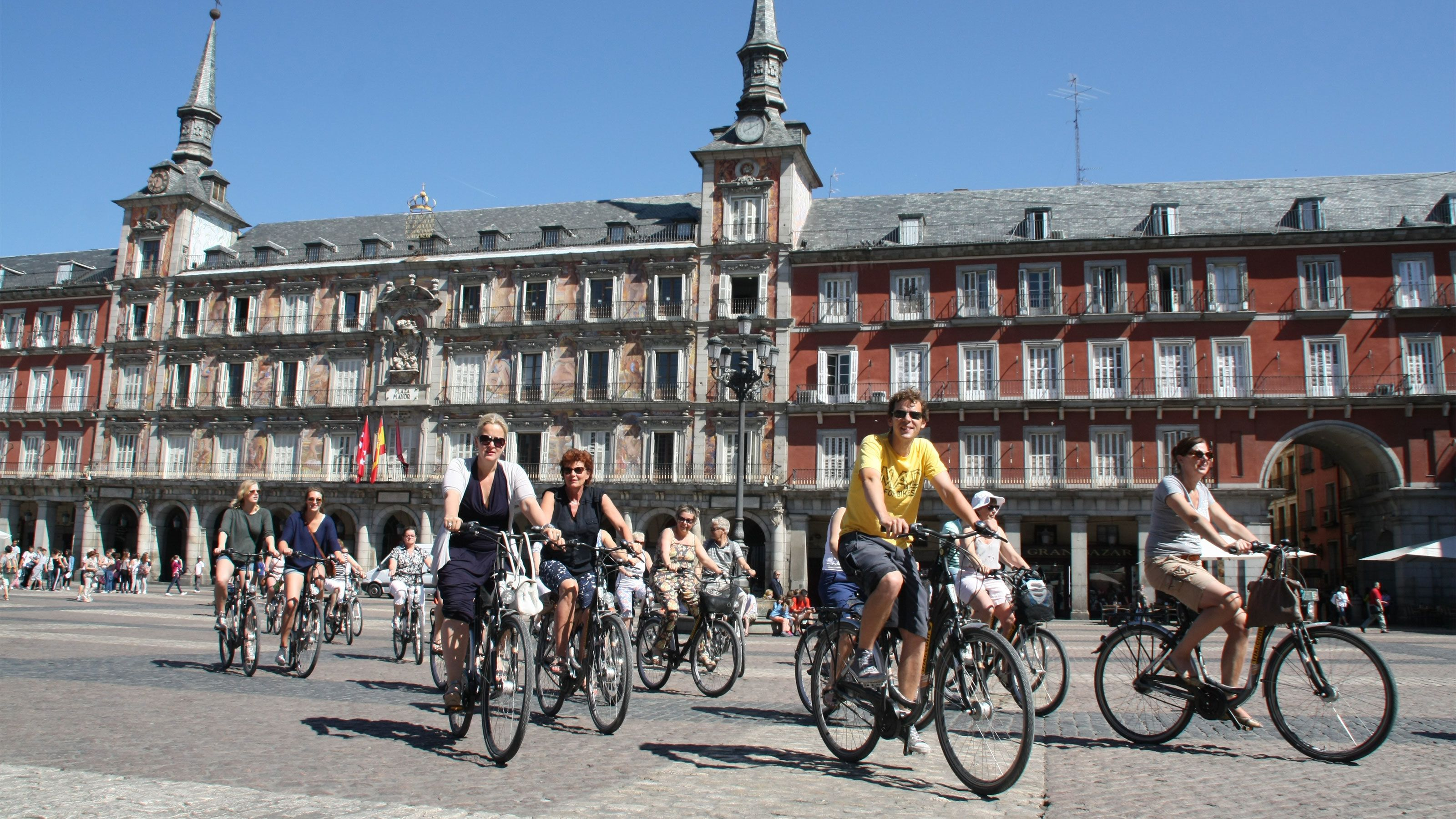 A group cycling through the Plaza Mayor Madrid during the daytime