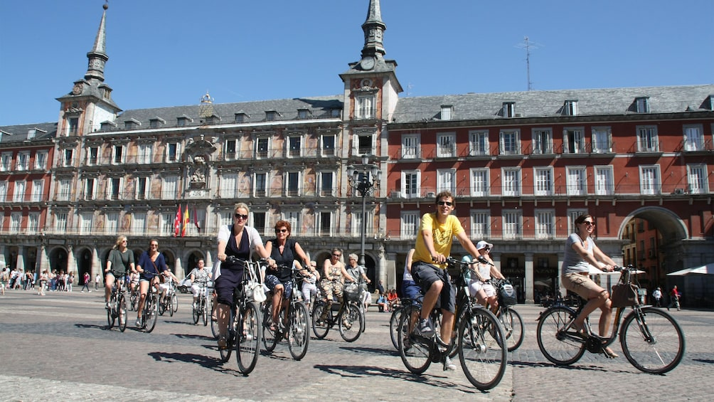 Apri foto 2 di 7. A group cycling through the Plaza Mayor Madrid during the daytime