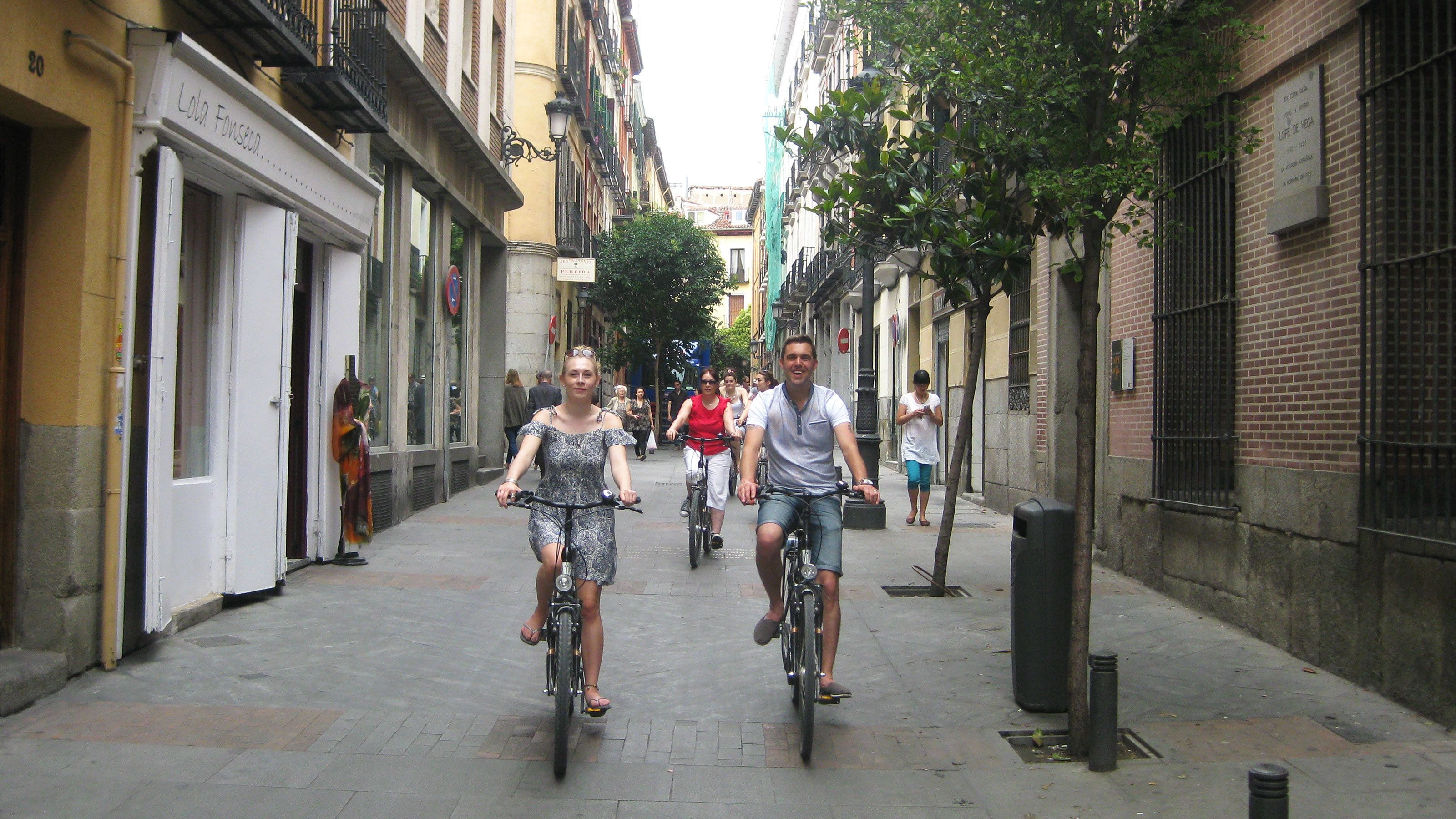 People riding bicycles down street in Madrid