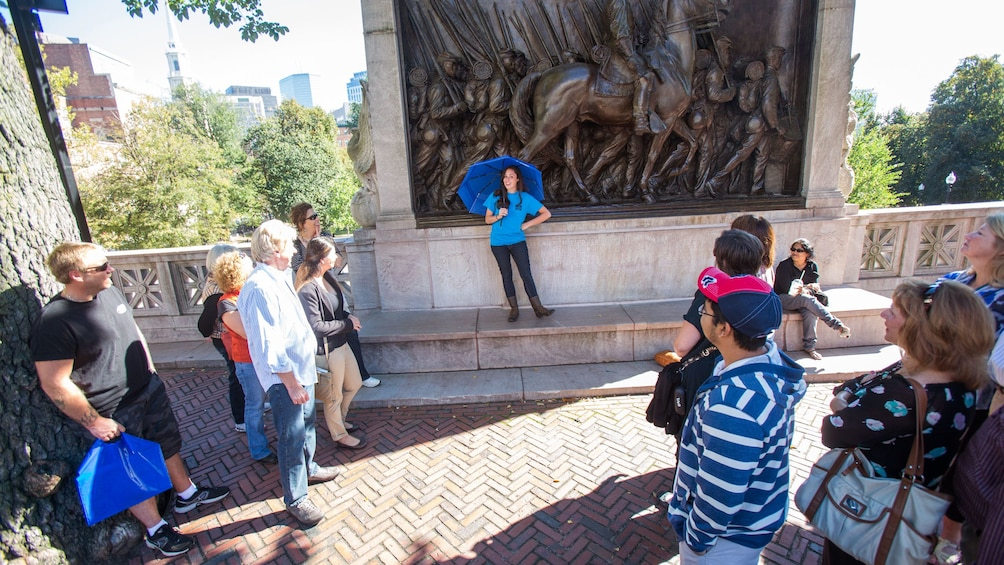 Show item 2 of 8. Tour guide with group at the Robert Gould Shaw Memorial at the edge of the Boston Common