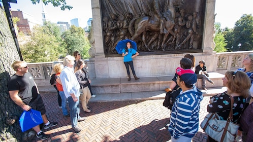 Tour guide with group at the Robert Gould Shaw Memorial at the edge of the Boston Common