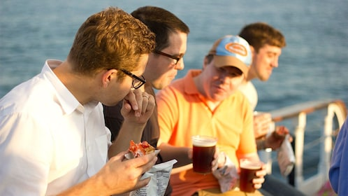 Group eating lobster on a sailboat in New York