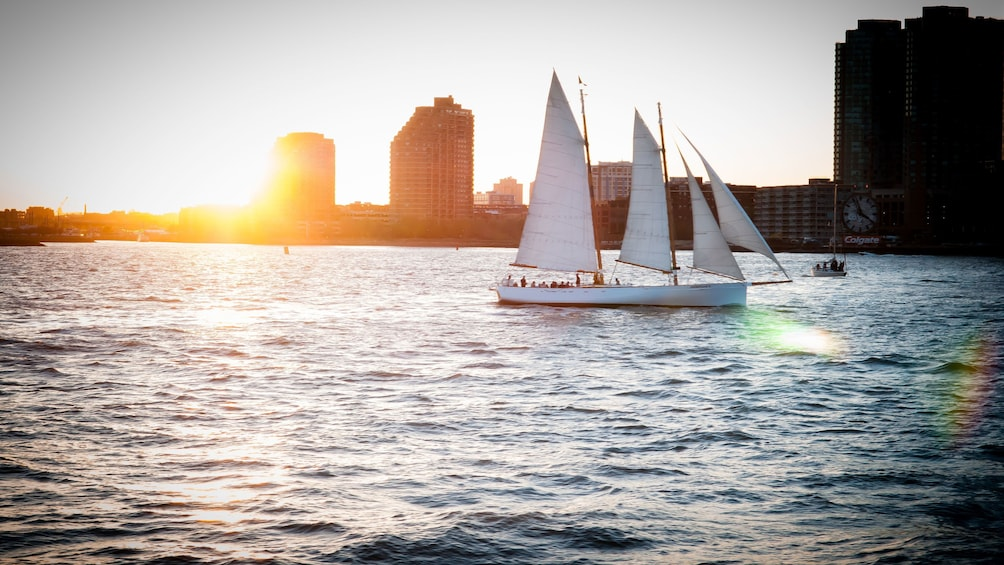 Show item 3 of 10. Sailboat with city in the distance at sunset in New York