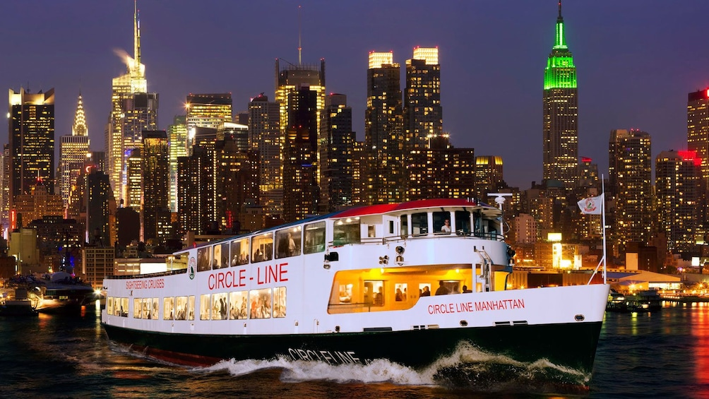 Apri foto 1 di 10. Sightseeing boat with the city in the background at night in New York