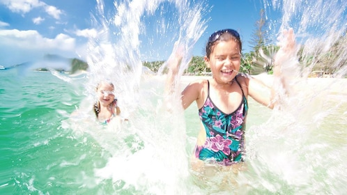 Kids splashing in the water in Tangalooma Dolphin Adventure Day Trip