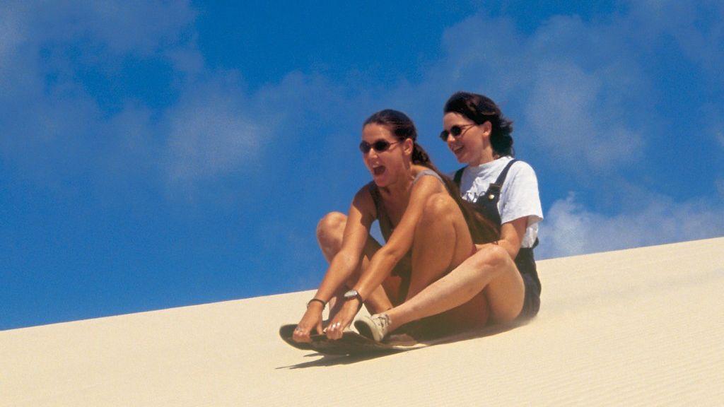 two women sledding on sane dune in Brisbane.