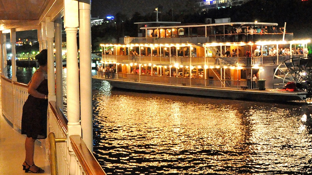 Show item 2 of 10. Woman looking at other boat during dinner cruise in Brisbane