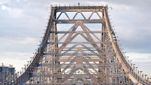 group of people climbing steep ladder on bridge in Brisbane