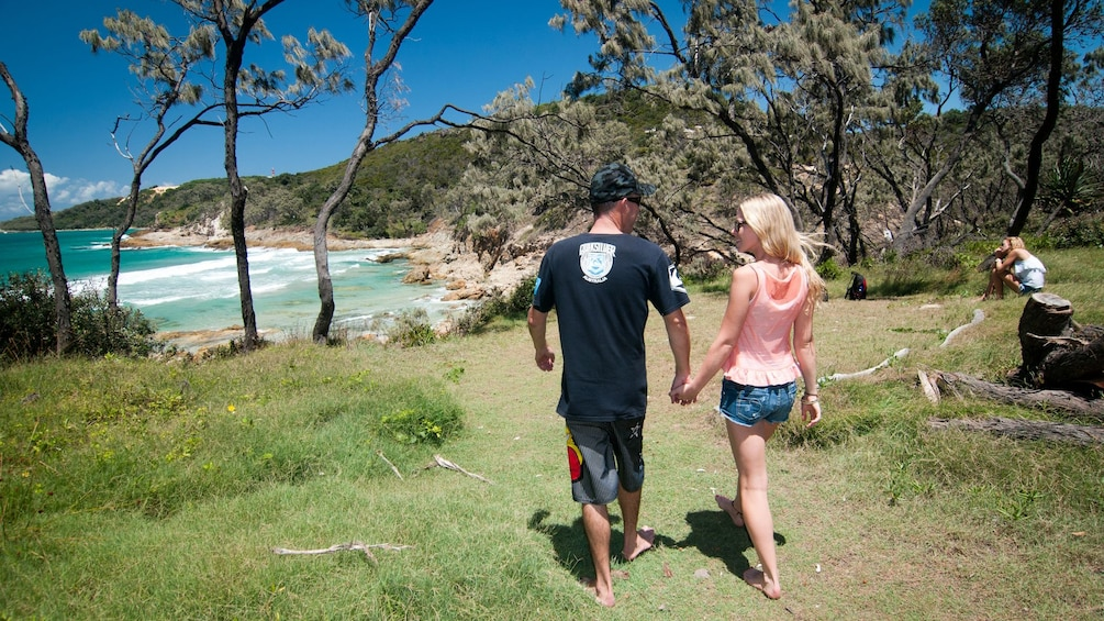 Young couple holding hands on sunny beach in Brisbane