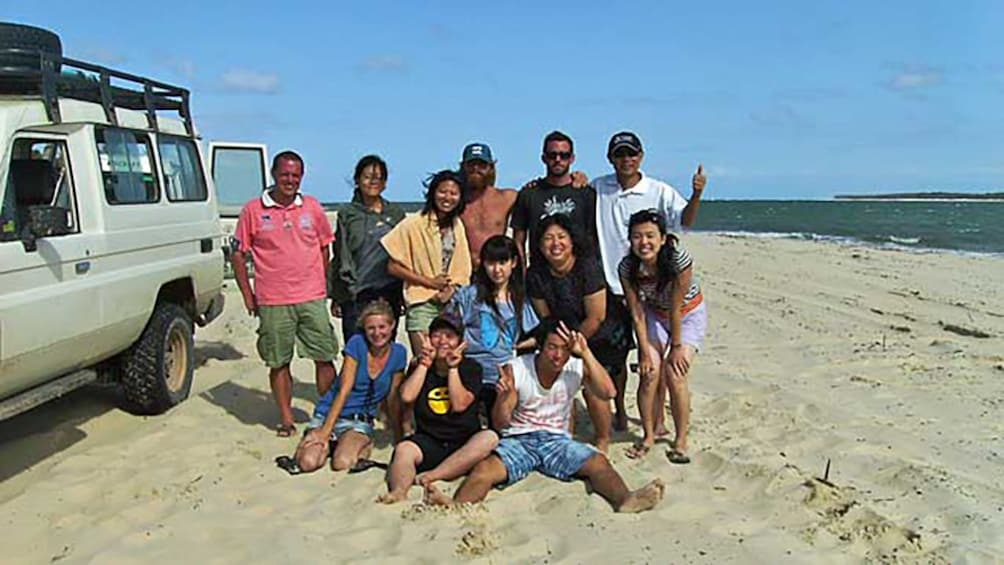 group of friends together on sandy beach of Brisbane
