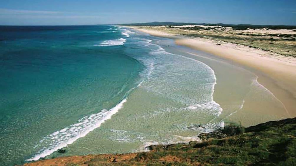 ocean surf breaking against beach in Brisbane