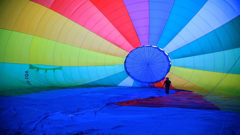 woman walks deep inside deflating hot air ballon in Byron Bay
