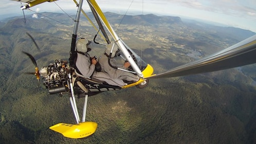 Two people experiencing a great view in a small open cockpit aircraft of Byron Bay.