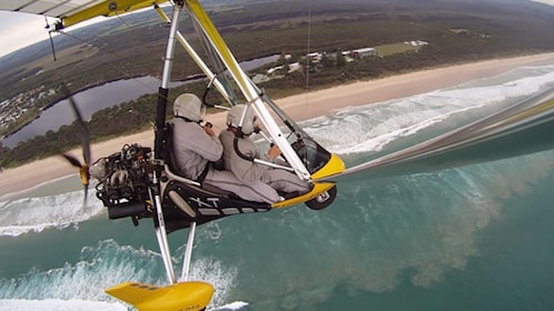 Thrill seekers taking pictures in a small open cockpit aircraft over Byron Bay.