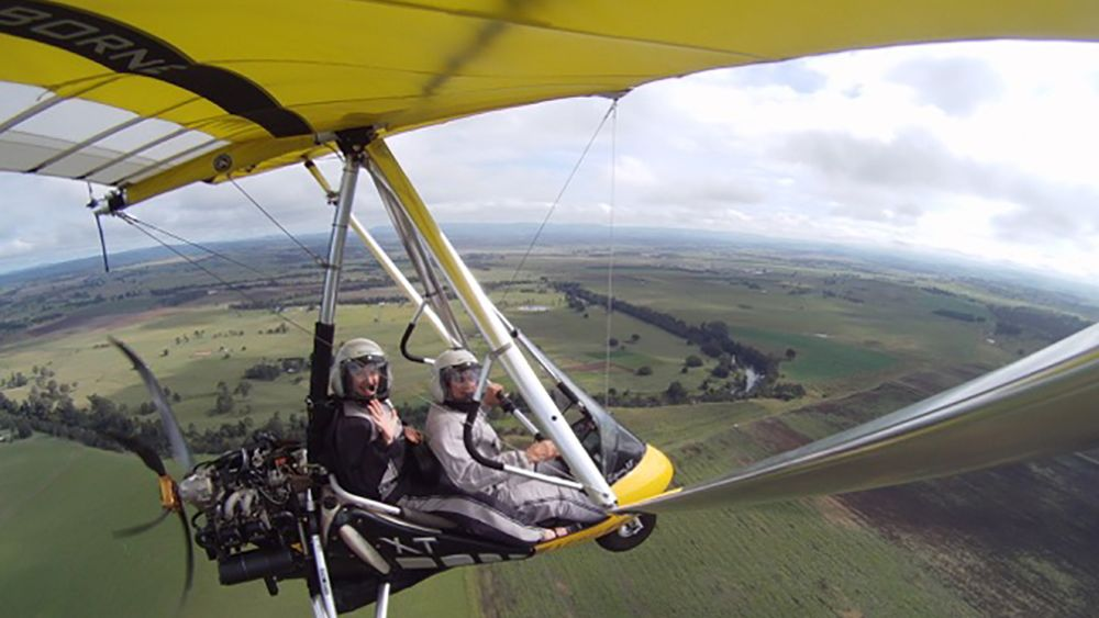 Cheery couple in a small open cockpit aircraft above Byron Bay area.