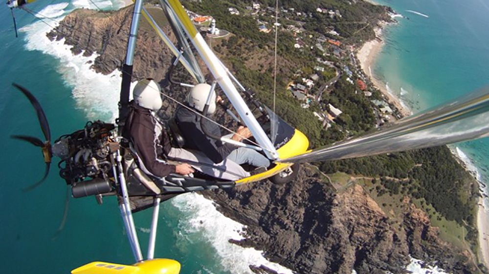 Aerial view of two people in a small open cockpit aircraft enjoying Byron Bay.