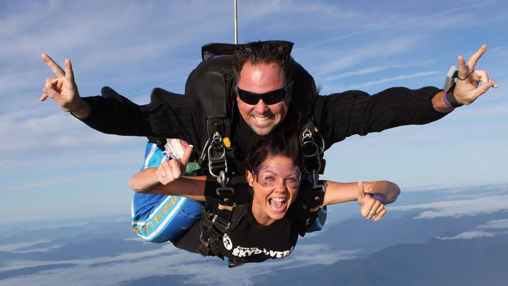 Show item 3 of 8. Couple doing the peace sign while on the Tandem Skydive Experience over Coffs Harbour in Australia