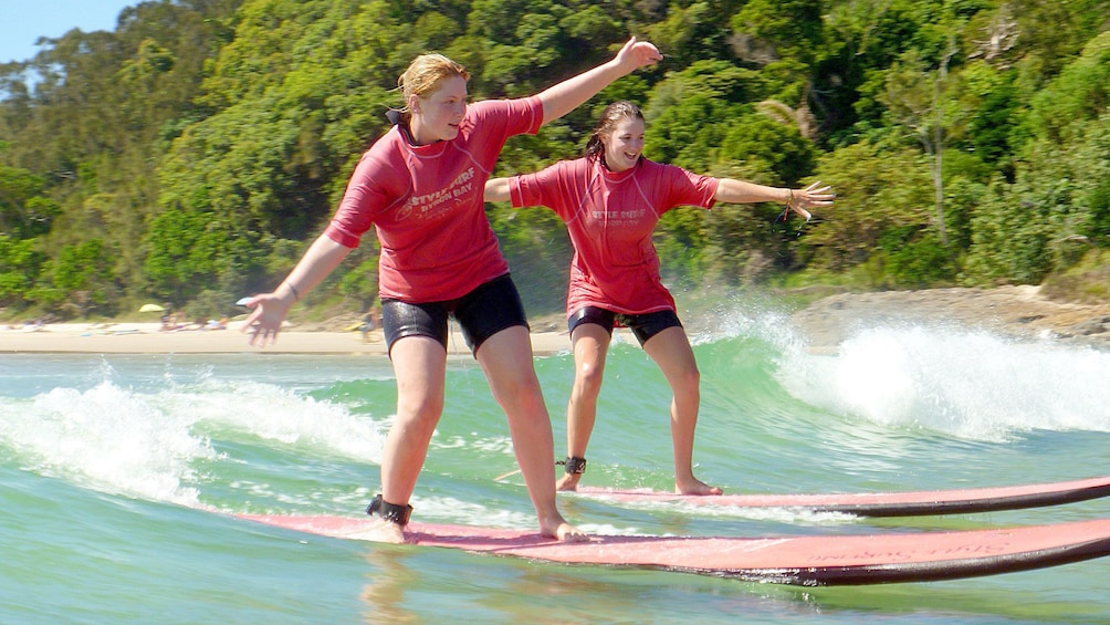Show item 1 of 5. Balancing girls learning how to surf of Byron Bay.