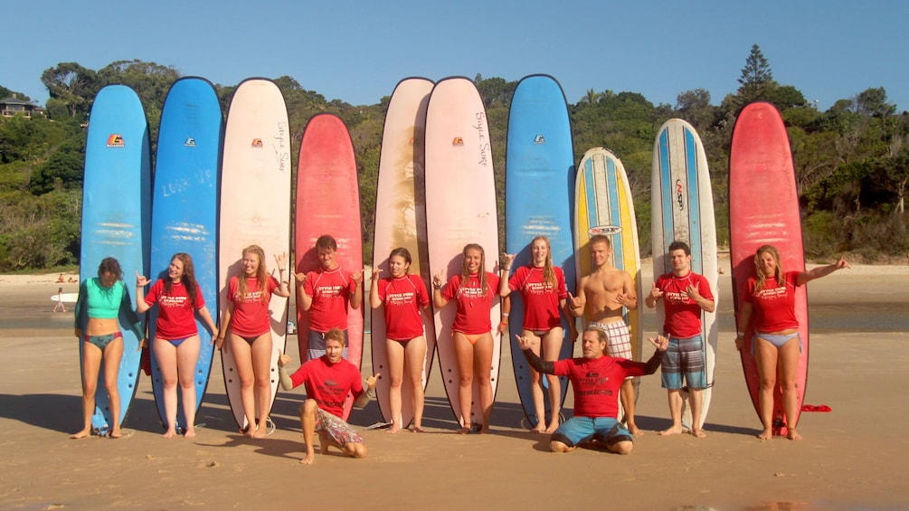 Show item 2 of 5. Pleasant group of surfers with surf boards behind them on Byron Bay beach.