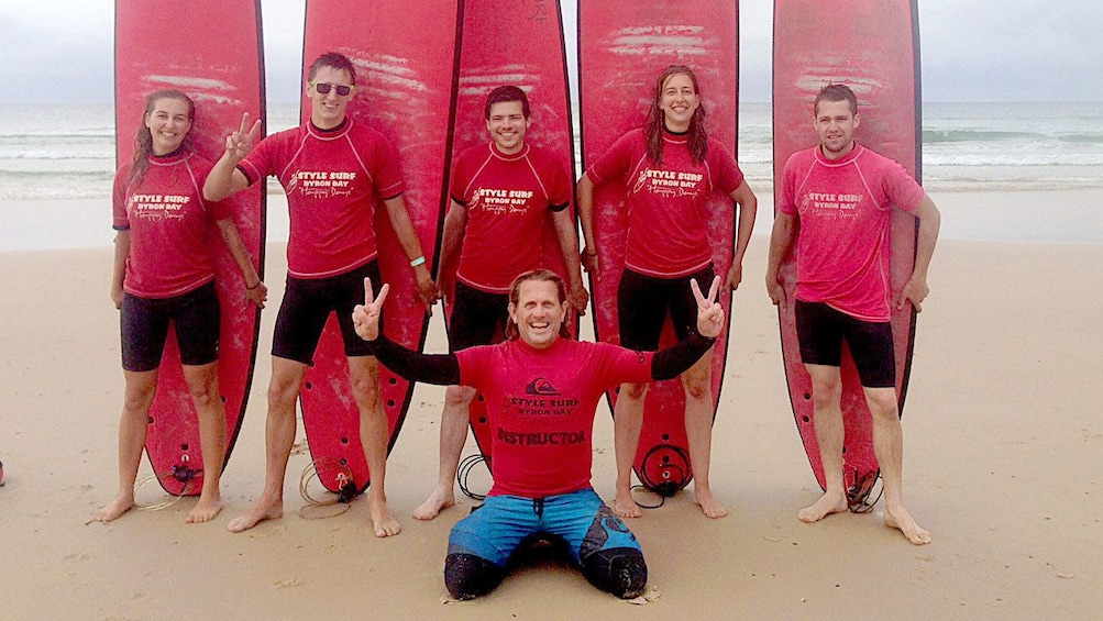 Show item 4 of 5. Happy group of student surfers with instructor on Byron Bay beach.