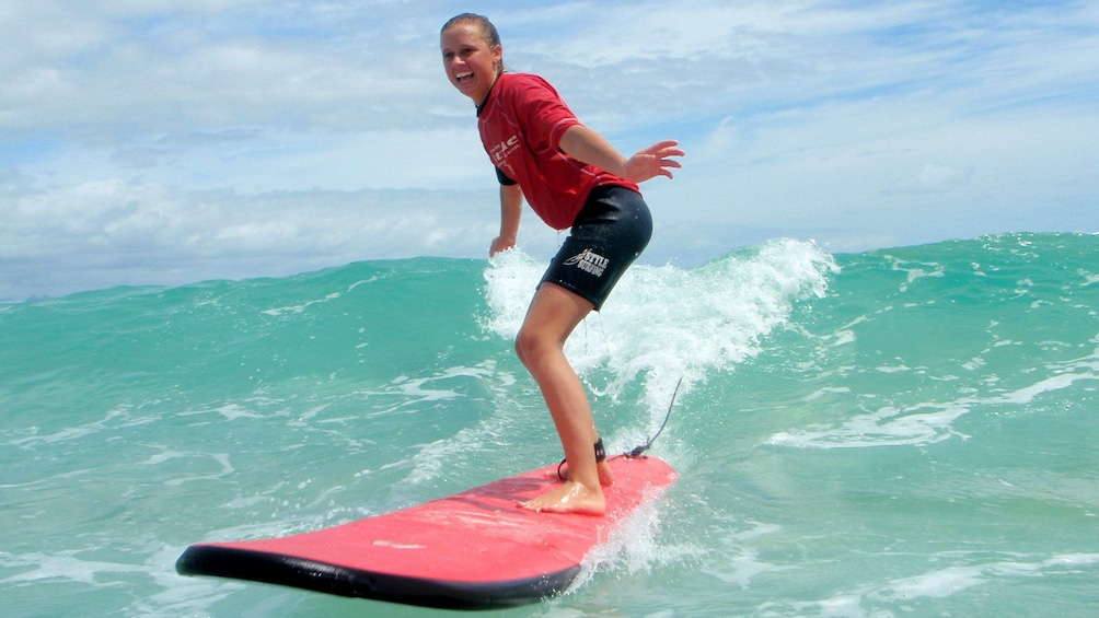 Show item 3 of 5. Young lady riding the waves in a group surfing lesson on Byron Bay.