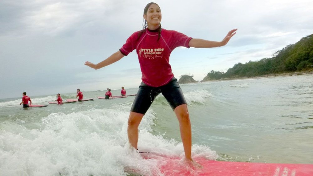Show item 5 of 5. Excited girl surfing in surfing lesson on Byron Bay.