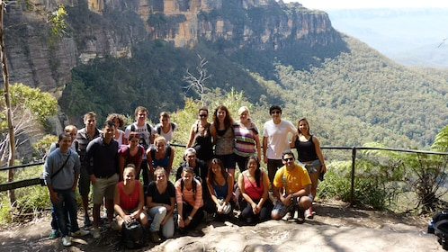group of people pose before rock formations in Blue Mountains