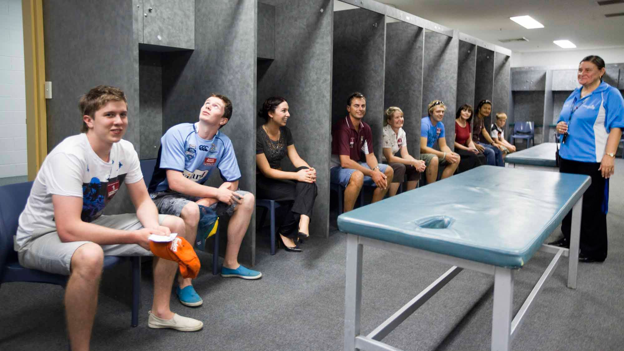 Many people sitting in locker room of stadium in Canberra