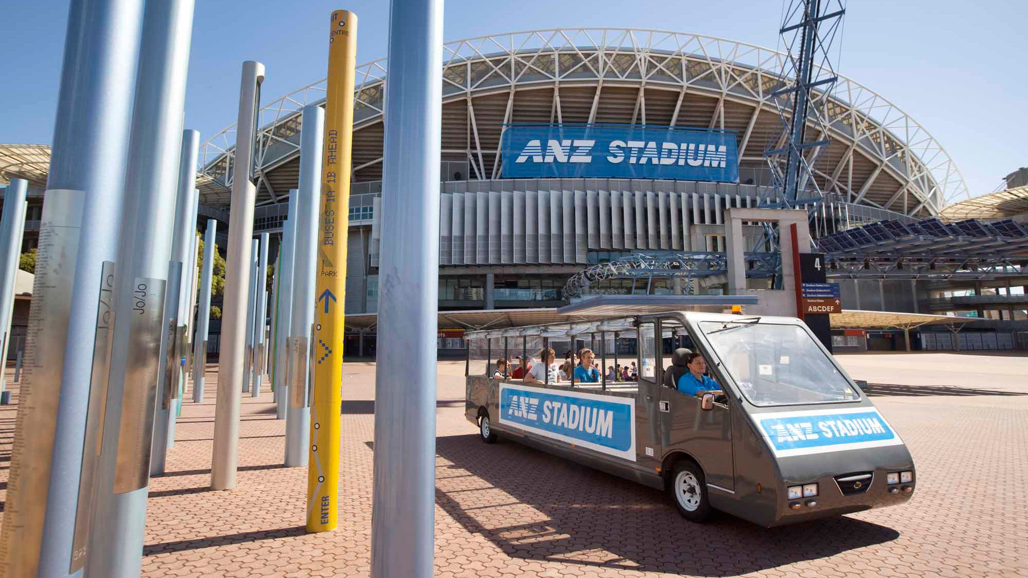 group of tourist in shuttle van by stadium in Canberra
