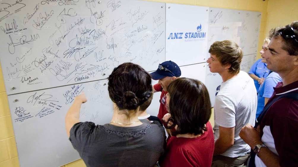 Show item 4 of 5. group of tourist looking at athlete signatures on white board in Stadium in Canberra