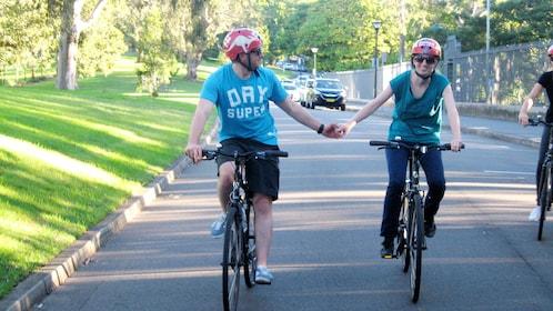 Couple holding hands on Sydney Harbour Bridge Ride Bike Tour in Australia.