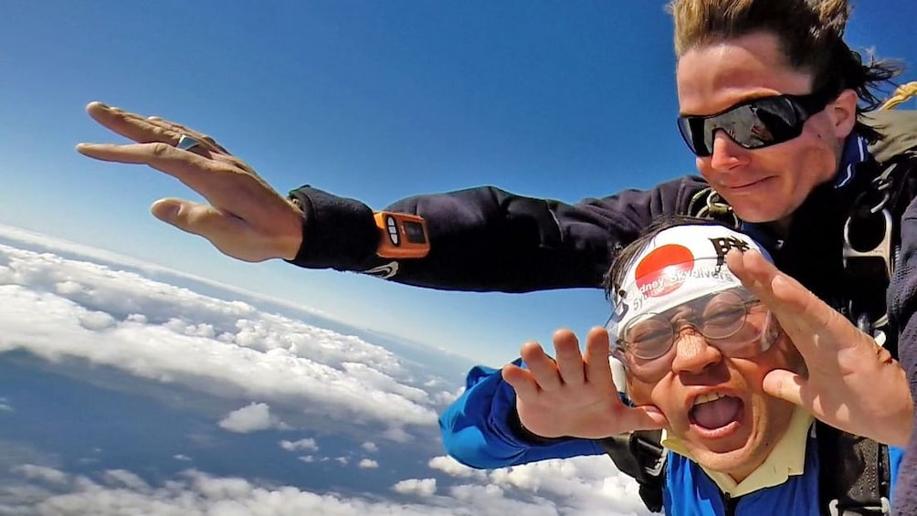 Show item 2 of 4. Two skydivers fastened together falling over Sydney.