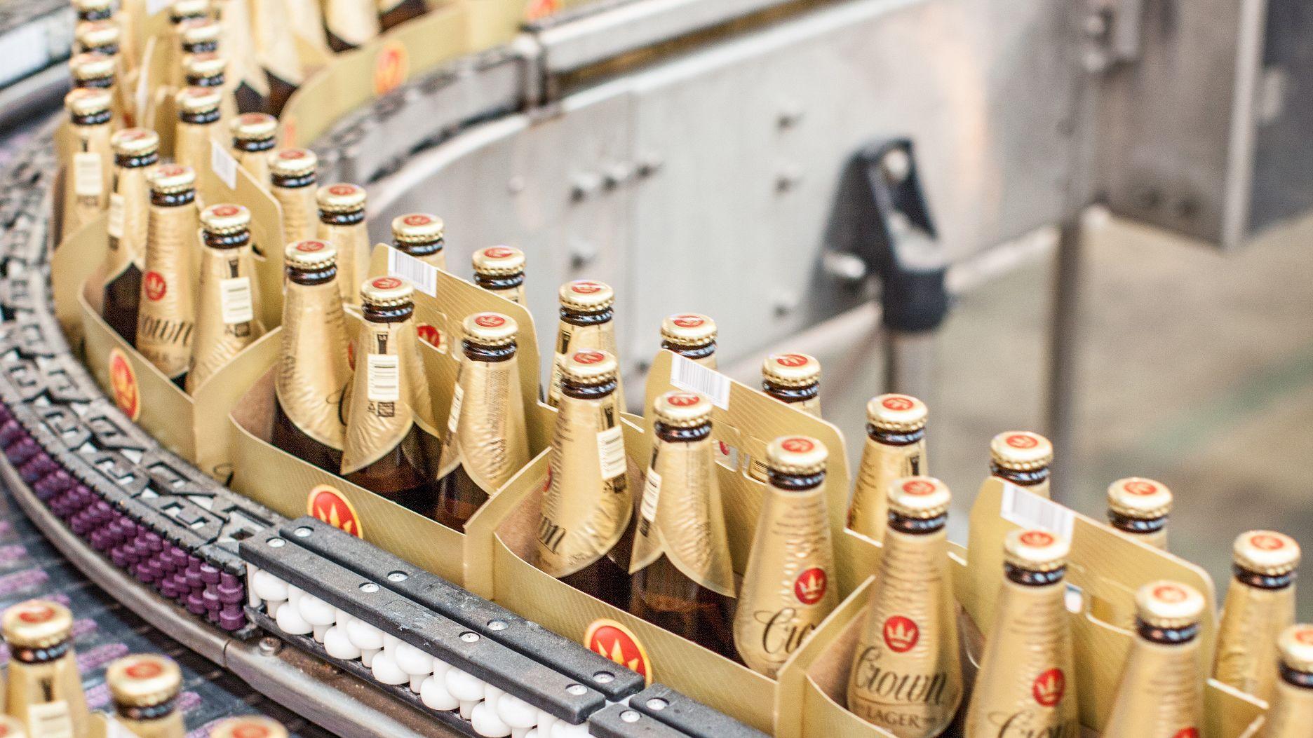 long neck beer bottles move along conveyor belt in brewery in Melbourne