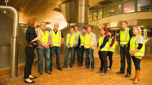 Tour guide briefs group of tourist inside brewery in Melbourne