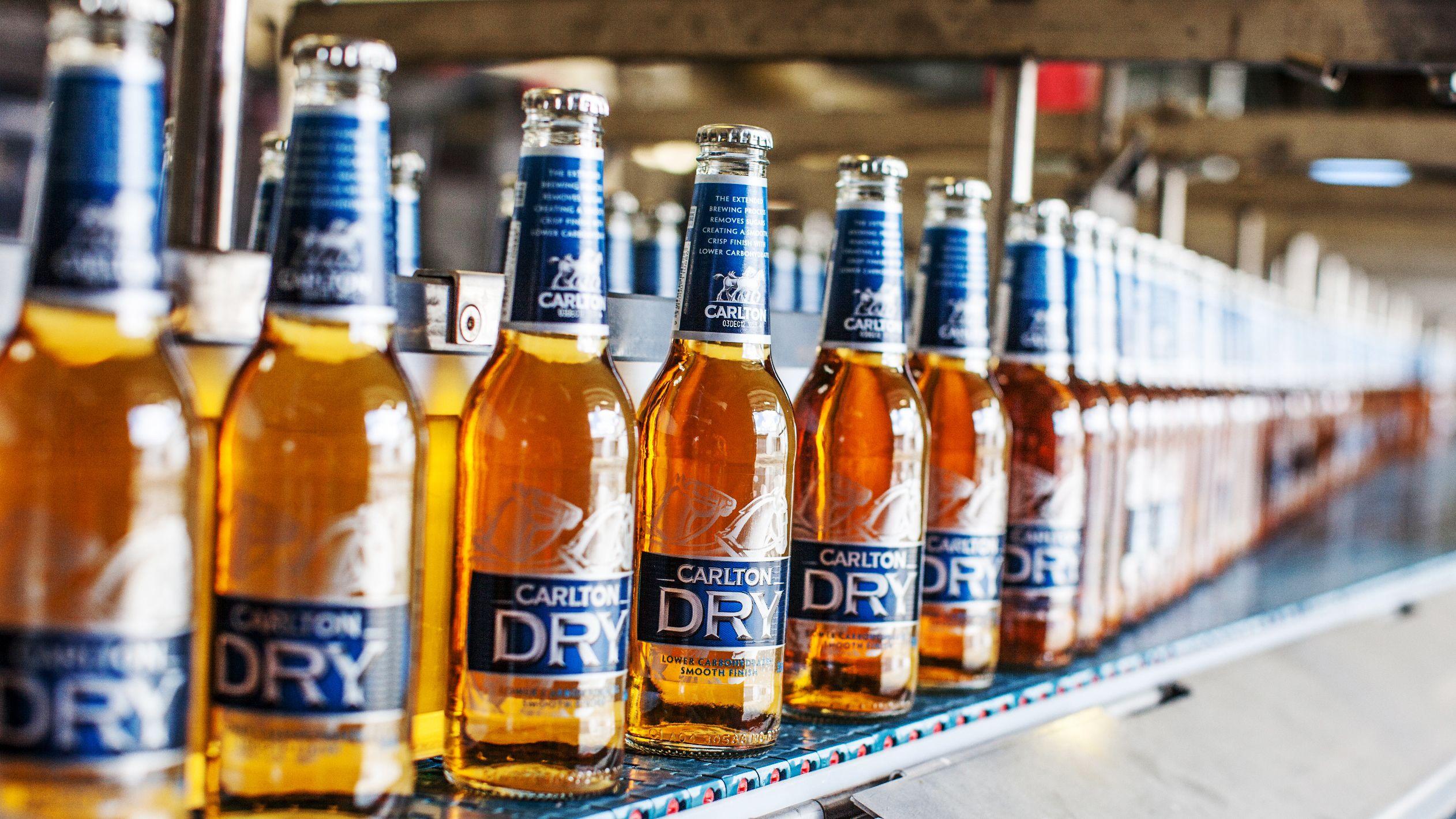 Long neck bottled beer run along convey belt in brewery in Melbourne