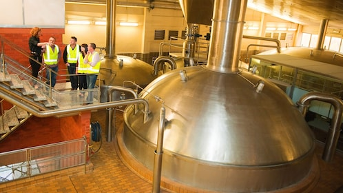 tour guide showing tourist huge boilers in brewery in Melbourne