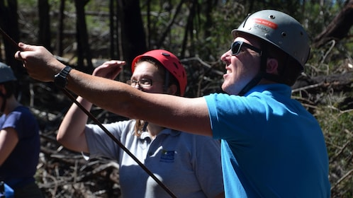 man in safety gear tests line of rock climbers in Melbourne