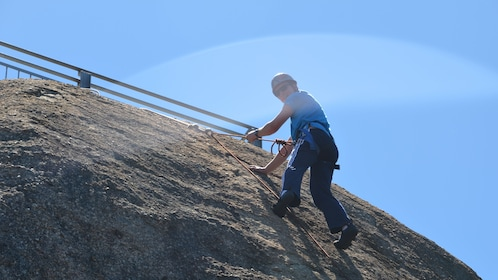 man in safety gear begins his descent of rocky wall in Melbourne