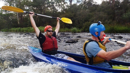 two men in Kayak paddle through rapids in Melbourne