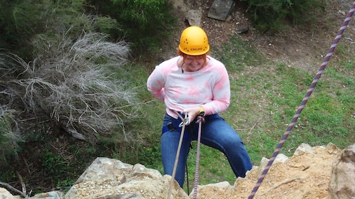 woman in safety harness repels down rock wall in Melbourne