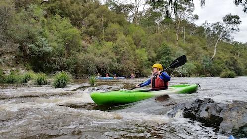 man in kayak paddles through river rapids in Melbourne