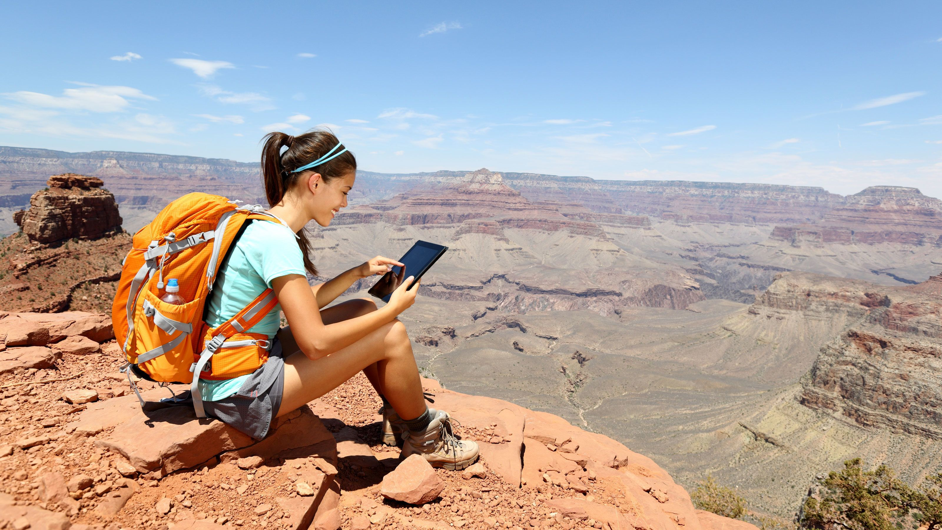 Woman capturing a memorable photo during her tour of the Grand Canyon