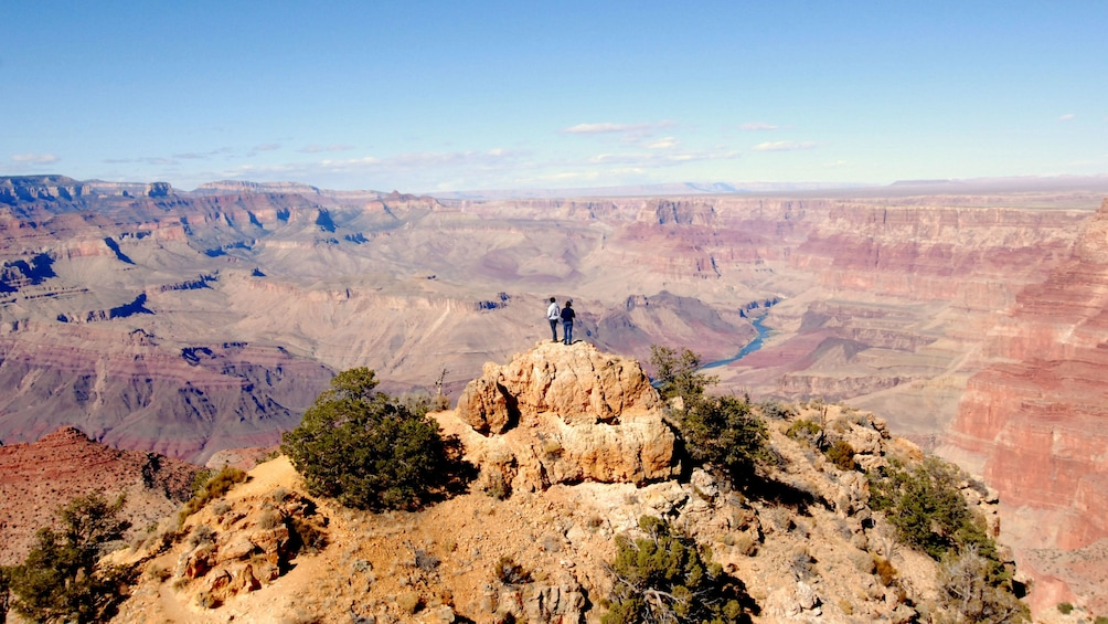 Show item 2 of 5. Couple basking the the vastness of the Grand Canyon