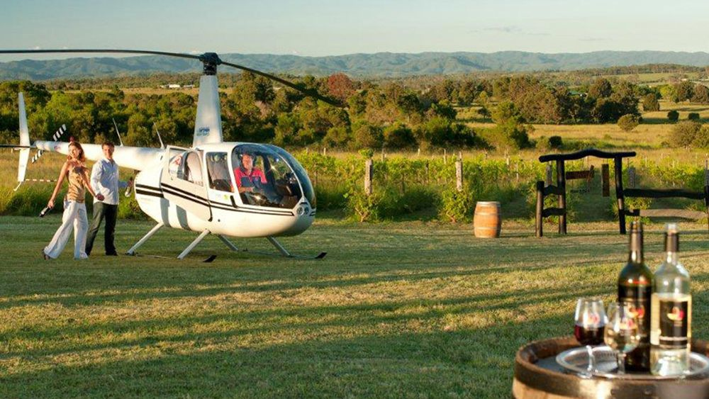 a couple at winery tour, enjoy stroling outside next to a helicopter in Gold Coast