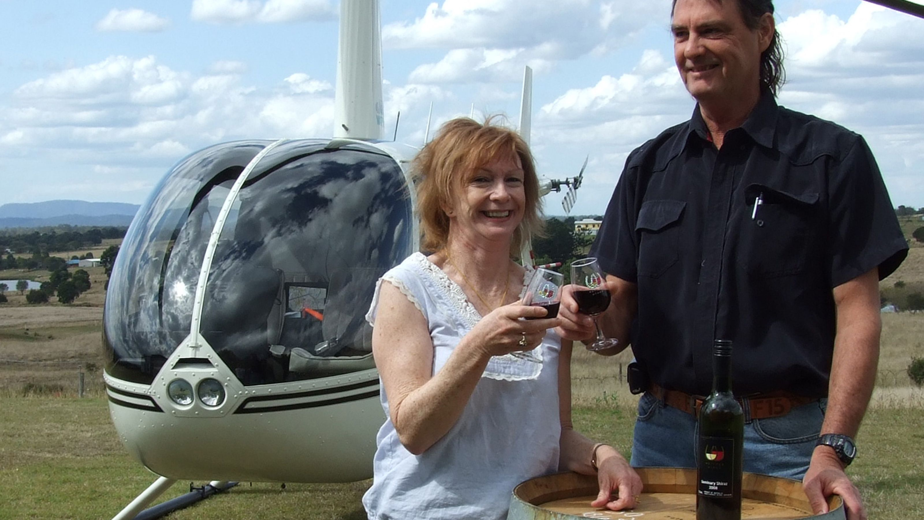 a couple enjoy glass of wine outside next to a helicopter in Gold Coast