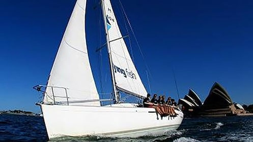group of passengers sit on deck of yacht in Sydney harbor