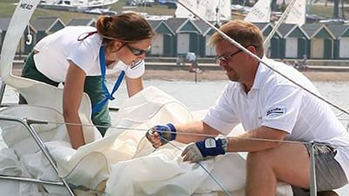 man and woman work rigging and sails aboard yacht in Sydney