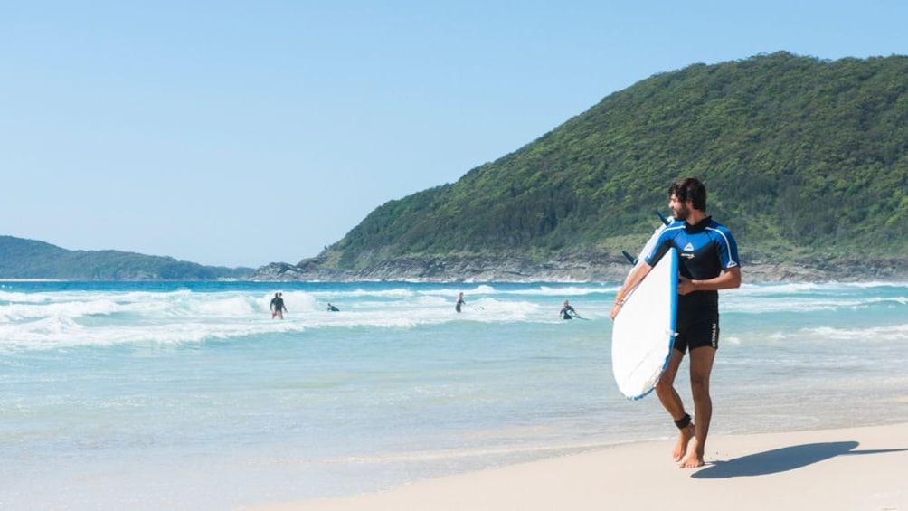 Surfer walking with surf board along beach in Sydney