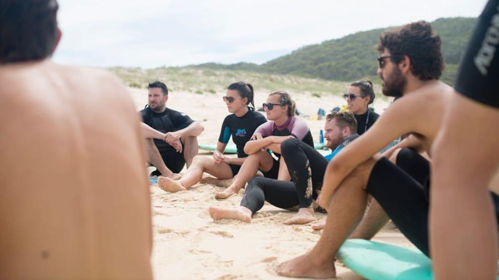 surf school students sitting on beach in Sydney